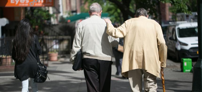 Two elderly men help each other walk down a street.