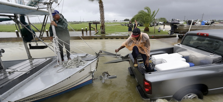 Tony Danos, left, and C.J. Johnson pull a shrimp boat out of the water, in anticipation of Tropical Storm Karen, at Myrtle Grove Marina in Plaquemines Parish, La., Friday, Oct. 4, 2013.