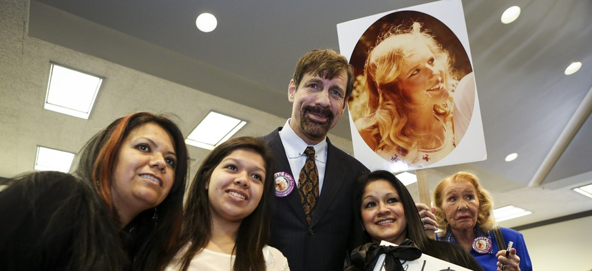 Dr. Henry T. Nicholas III, who has funded campaigns for Marsy's Law measures across the country, poses with victims of violence during the Orange County Victims' Rights March and Rally, Friday, April 26, 2013, in Santa Ana, Calif.