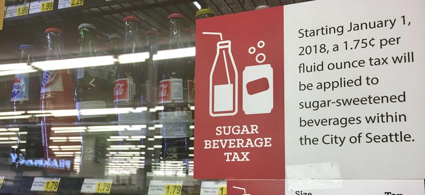 In this Sept. 24, 2018, a sign posted on a drink cooler in a store gives information about a soda tax that took effect in January, in Seattle.