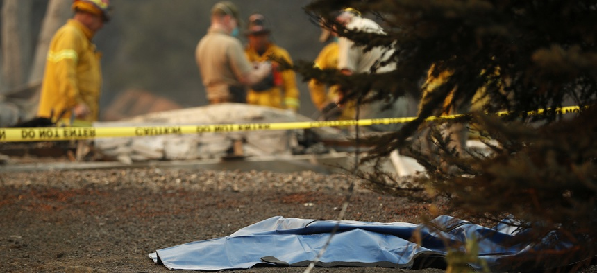 A bag containing human remains lies on the ground as officials continue to search at a burned out home at the Camp Fire, Sunday, Nov. 11, 2018, in Paradise, Calif.