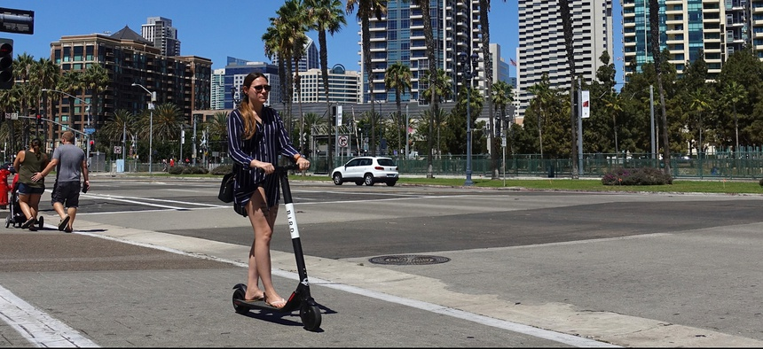 A woman rides a scooter in San Diego.