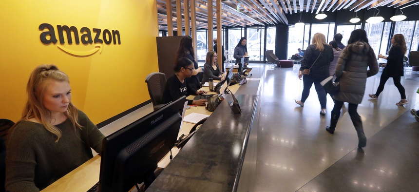 Employees walk through a lobby at Amazon's headquarters Tuesday, Nov. 13, 2018, in Seattle.