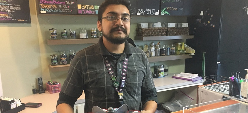 Budtender Rico Vasquez stands behind a counter displaying recreational pot products for sale at Smokey's: A 4:20 House in Garden City, Colorado. Sales at marijuana dispensaries have created a tax revenue bonanza for the tiny town.