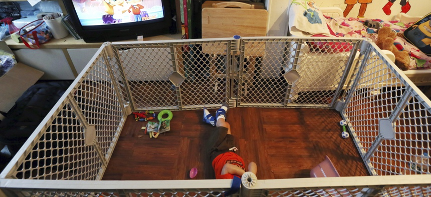 In this July 28, 2017, photo, Alexander, 2, a disabled foster child, lies on a mat in a playpen at his foster home in Philadelphia.