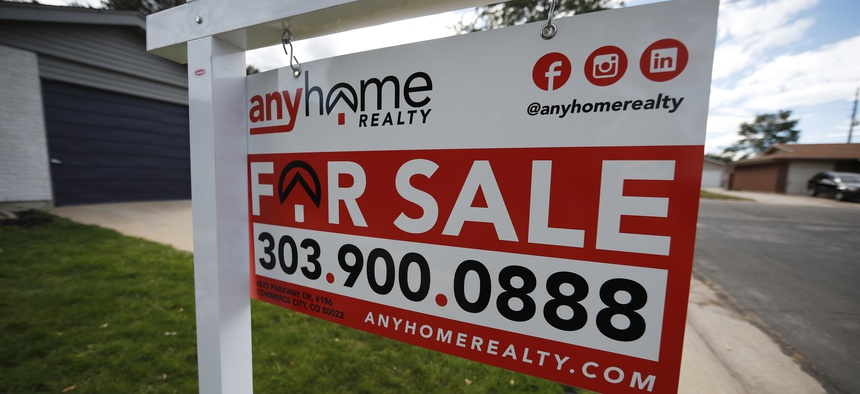 In this Oct 2, 2018, photo a for sale sign stands outside a home on the market in a suburb north of Denver.