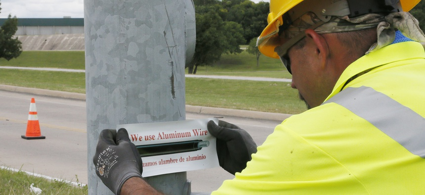 In this Thursday, June 22, 2017 photo, David Tubb puts a sticker on the base of a streetlight where new aluminum wiring has been installed in Tulsa, Okla. The city has lost 33 miles of streetlight wiring to thieves stealing copper wire.