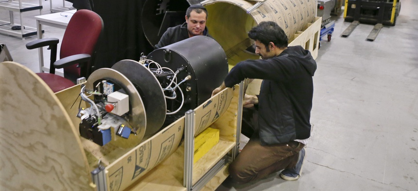 In this April 4, 2018 photo, David Kohandash, left, and Mohammad Mousaei work on the RadPiper robot in the robotics institute at Carnegie-Mellon University in Pittsburgh.
