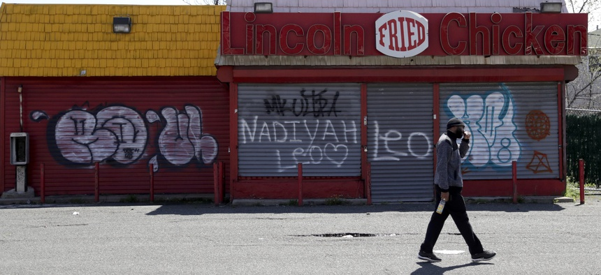 In this April 26, 2018, photo a man walks by a closed restaurant along Bergen Street in an Opportunity Zone in Newark, N.J.
