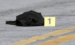 A Los Angeles County Sheriff's forensics photo evidence marker is positioned next to clothing littering a street in Altadena, Calif., July 6, 2016.