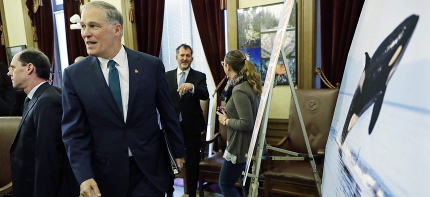 Washington Gov. Jay Inslee walks past a photo of an orca whale after he talked to reporters about his 2019-2021 budget proposal, Thursday, Dec. 13, 2018, at the Capitol in Olympia, Wash.