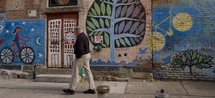 A man passes a mural at Rockaway Brewing Company in Long Island City, a part of Queens in NYC that is a longtime industrial and transportation hub that has become a fast-growing neighborhood of riverfront high-rises and redeveloped warehouses.