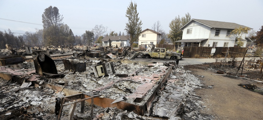 Houses remain standing and with little damage in view of others that were destroyed in a wildfire several days earlier, Tuesday, Sept. 15, 2015, in Middletown, Calif.