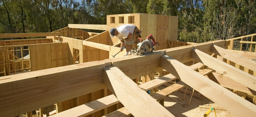 A carpenter hammers nails into the central beam while framing in southern California.