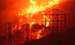 A wildfire burns near power lines in Sycamore Canyon near West Mountain Drive in Montecito, California on Dec. 16, 2018.