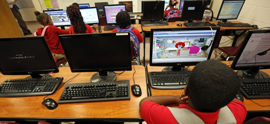 In this Oct. 23, 2014 photograph, a young boy uses a computer during an after-school session at the Durant elementary school in Durant, Miss.