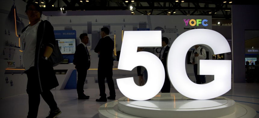 Visitors stand near a 5G logo at a display for Chinese fiber optic cable maker YOFC at the PT Expo in Beijing, Sept. 26, 2018.