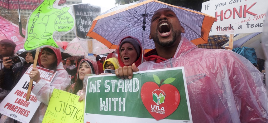 Teachers and supporters hold signs in the rain during a rally Monday, Jan. 14, 2019, in Los Angeles