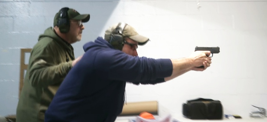 In this photo taken from a video shot on Nov. 28, 2018, a man fires a gun at the American Tactical Systems' indoor range in Green Island, New York.