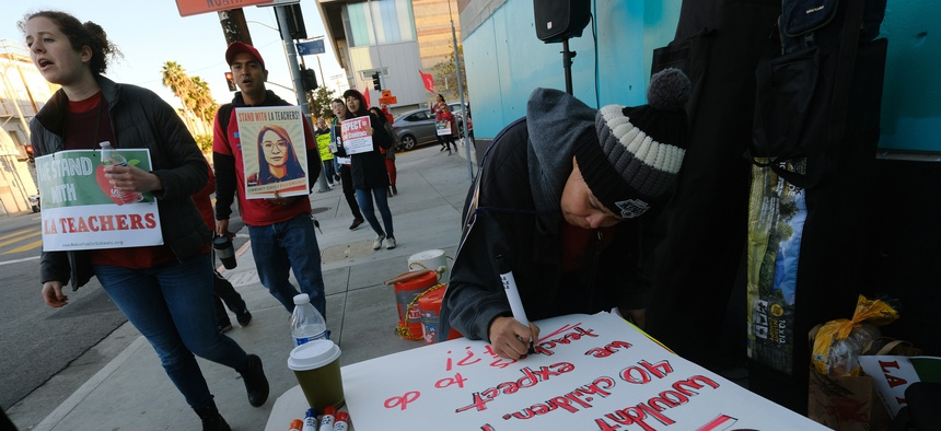 Rosa Companioni prepares a rally sign in support of Los Angeles school teachers Tuesday, Jan. 22, 2019, in Los Angeles.