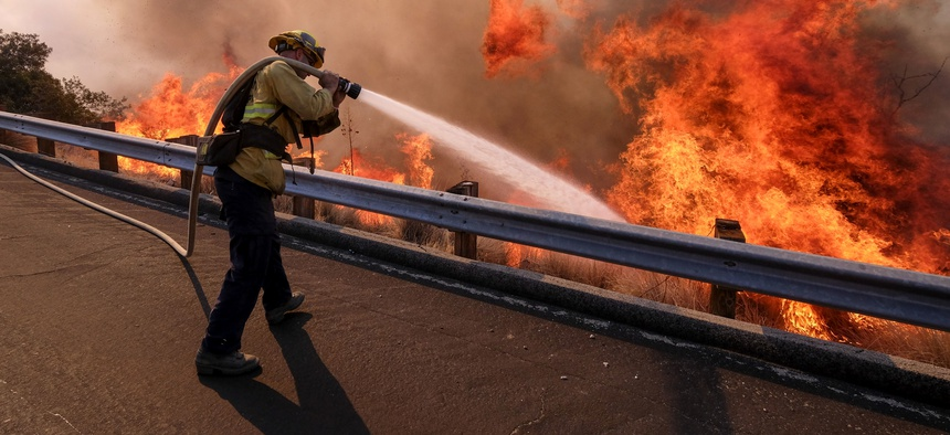 A firefighter battles a fire along the Ronald Reagan Freeway, aka state Highway 118, in Simi Valley, Calif. on Nov. 12, 2018.