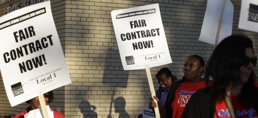 This Sept. 10, 2012 file photo shows Chicago teachers walk walking a picket line outside a school in Chicago, after they went on strike for the first time in 25 years.