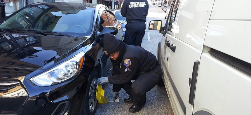 Cpl. Tiffany Chambers of the Baltimore transportation department clamps a self-release parking boot on a car on a downtown street last month.