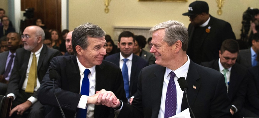 North Carolina Gov. Roy Cooper, left, and Massachusetts Gov. Charlie Baker shake hands Wednesday after testifying before the House Natural Resources Committee hearing on climate change in Washington, D.C.