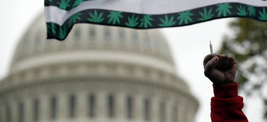 A man holds up a joint during a rally in Washington, D.C. to support the legalization of marijuana in 2017.