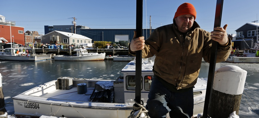 Lobsterman Jim Buxton climbs up from a dock where after checking on the bilge pump on his lobster fishing boat during frigid temperatures, Thursday, Jan. 31, 2019, in Portland, Maine.