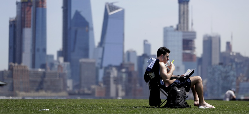 Part of the New York City skyline gives backdrop to a man as he sips on a drink while sunbathing on a warm day at Pier A Park on May 2, 2018, in Hoboken, N.J.