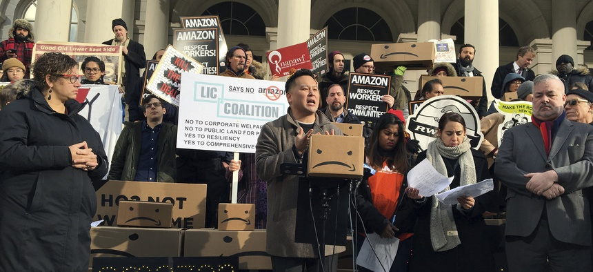 This Dec. 12, 2018 file photo shows State Assemblyman Ron Kim, center, as he speaks at a rally opposing New York's deal with Amazon, on the steps of New York's City Hall.