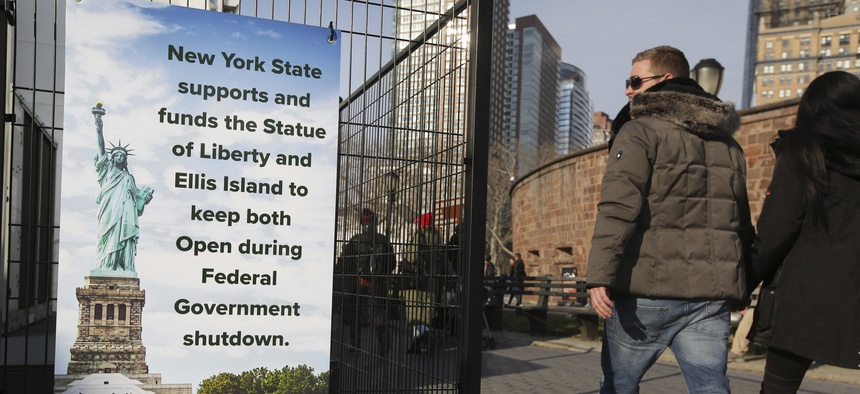 Tourists walk past a sign near the Statue of Liberty in New York, during the most recent federal government shutdown. States such as Arizona, New York and Utah have spent state money to keep national parks open during shutdowns.