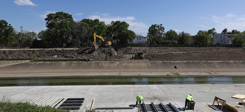 Construction workers excavate and widen Brays Bayou as part of a nearly $500 million flood control project on March 22, 2018, in Houston.