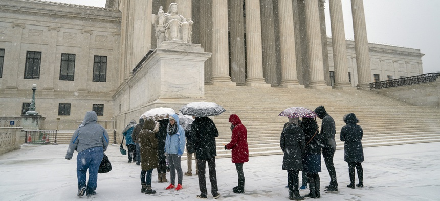 Visitors wait to enter the Supreme Court Wednesday as a winter snow storm hits the nation's capital. The court that morning ruled in the case of an Indiana man whose Land Rover was seized by police.