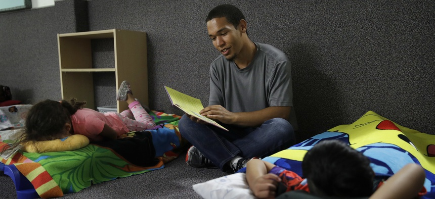 In this Sept. 14, 2017, photo, Darian Tharp reads during bedtime at the McCarran International Child Development Center, a 24-hour daycare in Las Vegas.