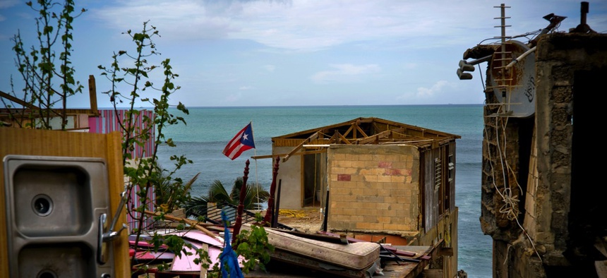 A Puerto Rican national flag is mounted on debris of a damaged home in the aftermath of Hurricane Maria in the seaside slum La Perla, San Juan, Puerto Rico.