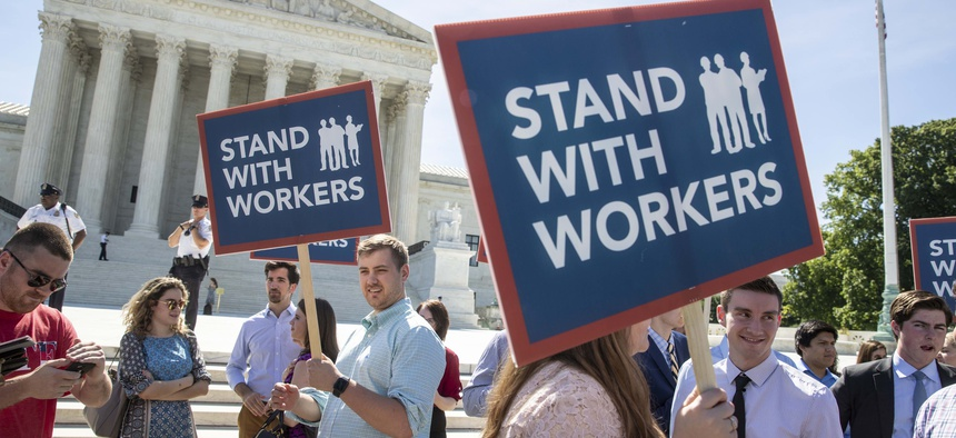 In this Monday, June 25, 2018 file photo, people gather at the Supreme Court awaiting a decision in an Illinois union dues case, Janus vs. AFSCME, in Washington.