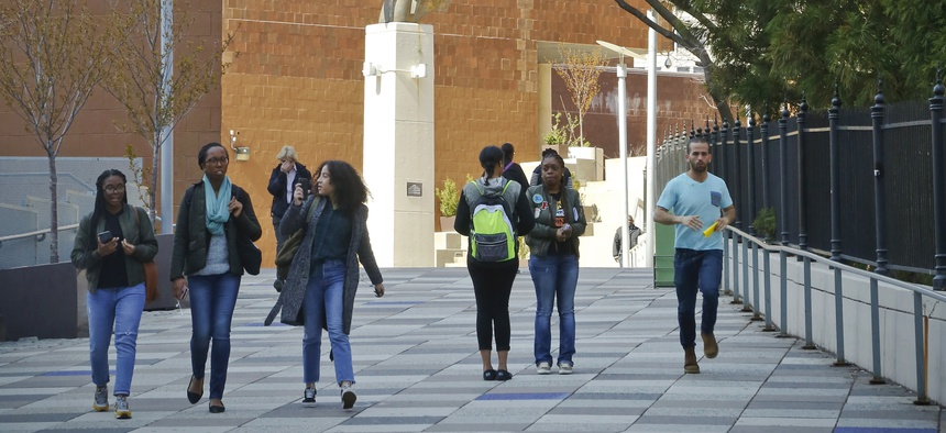 People walk near the main entrance to the Borough of Manhattan Community College in New York. At least 15 states, including New York, offer grants that allow some students to attend public colleges tuition-free.