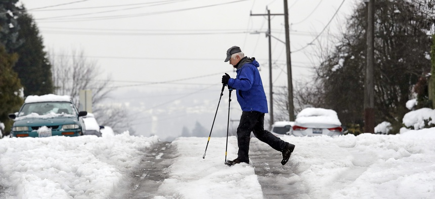A pedestrian crosses a street where a foot or so of snow is turning to slush on Feb. 12, 2019, in Seattle.