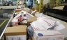 Packages travel on a conveyor belt for sorting at the main post office in Omaha, Neb.