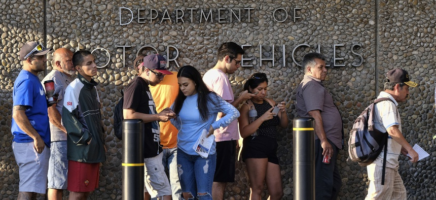 In this Aug. 7, 2018, file photo, people line up at the California Department of Motor Vehicles prior to opening in the Van Nuys section of Los Angeles.