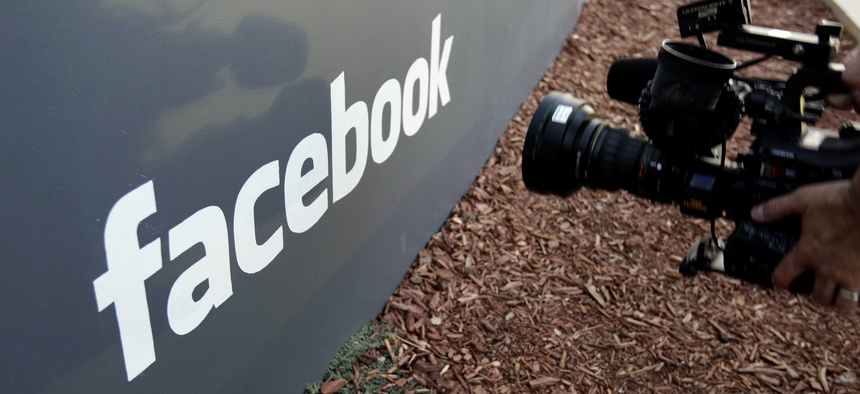 A television photographer shoots the sign outside of Facebook headquarters in Menlo Park, Calif.