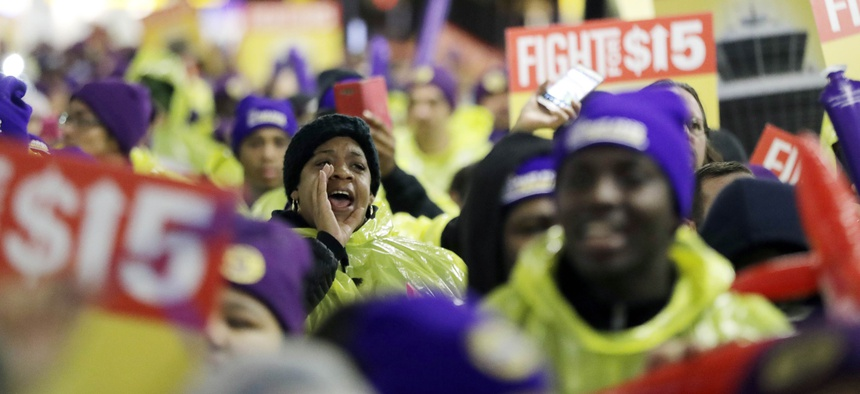 A woman shouts while marching with service workers asking for $15 minimum wage pay during a rally at Newark Liberty International Airport, Tuesday, Nov. 29, 2016, in Newark, N.J.