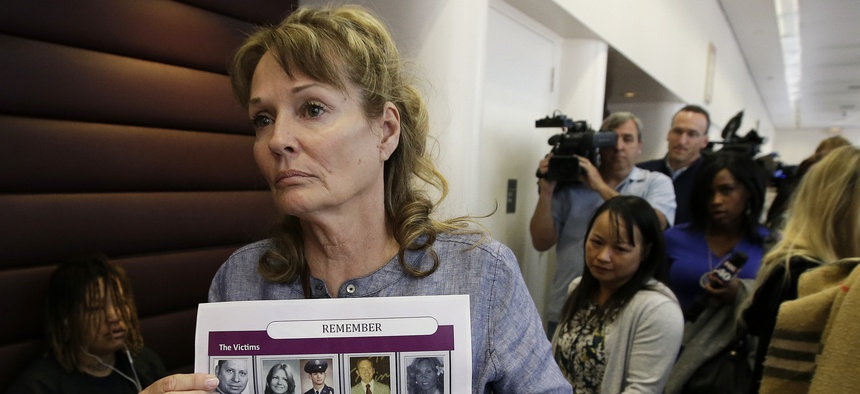 In this May 14, 2018, file photo, Melanie Barbeau displays photos of murder victims believed to be slain by the Golden State Killer as she leaves a hearing for suspect Joseph DeAngelo in Sacramento, Calif.
