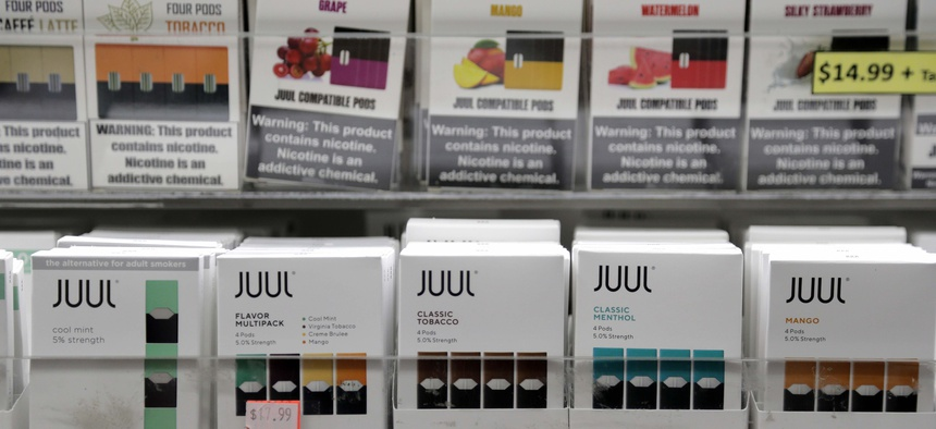 Juul products, bottom row, are displayed at a smoke shop in New York, Thursday, Dec. 20, 2018.