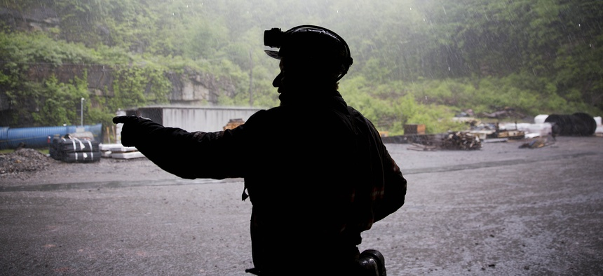 Coal miner Scott Tiller takes shelter from the rain after coming out of an underground mine at the end of a shift in Welch, W.Va.