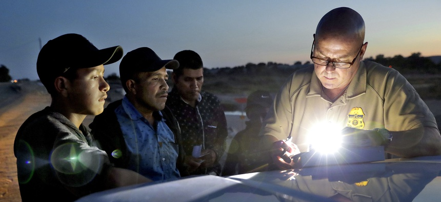In this July 18, 2018, file photo, a U.S. Customs and Border Patrol agent gathers information on four Guatemalan nationals, including two men and a pair of 12 and 13-year-old boys in Yuma, Ariz.
