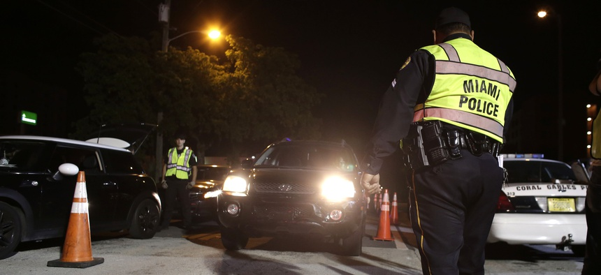 A Miami police officer guides vehicles through a 2015 drunk-driving checkpoint in Miami.