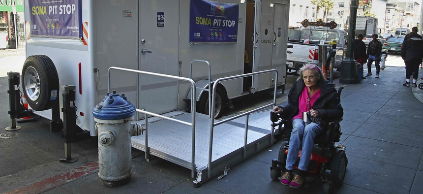 "In this photo taken on Thursday, April 26, 2018, a woman in a wheelchair passes a ""Pit Stop"" public restroom facility in San Francisco."